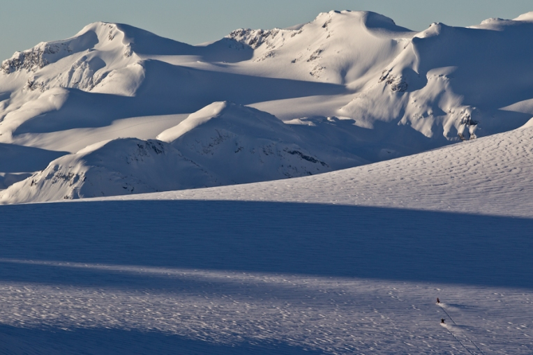 Helen Schettini and Clint Allan riding across the Pemberton Glacier on snowmobiles.